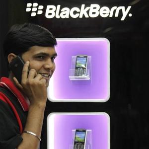 Homem fala em smartphone BlackBerry em frente a uma loja da marca em Kolkata, na Índia