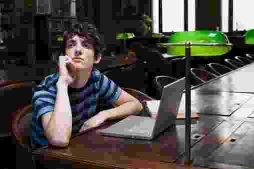 Adolescente usa computador em biblioteca - Getty Images
