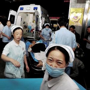 Vítima é retirada de fábrica da Foxconn em Chengdu, na China: a fábrica de iPads teve uma explosão, que matou 2 pessoas e feriu dezenas