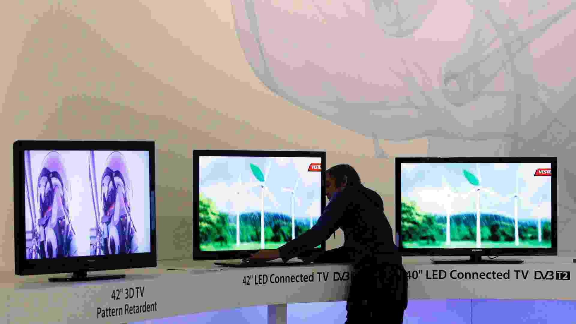 Técnico arruma aparelhos de TV antes da abertura da feira de eletrônicos de consumo IFA, realizada de 2 a 7 de setembro em Berlim - 31.ago.11 - Thomas Peter/Reuters