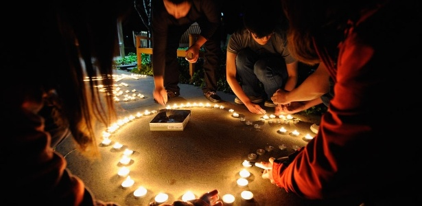 Chineses que estudam nos Estados Unidos usam velas para homenagear Steve Jobs em Cupertino, Califórnia, onde fica a sede da empresa